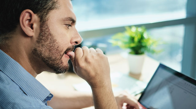 anxious businessman biting nails working. does cbd oil help relieve anxiety?