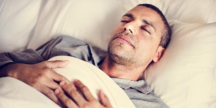 man sleeping on a bed. cbd gummies for sleep and anxiety. buy cbd gummies online usa.