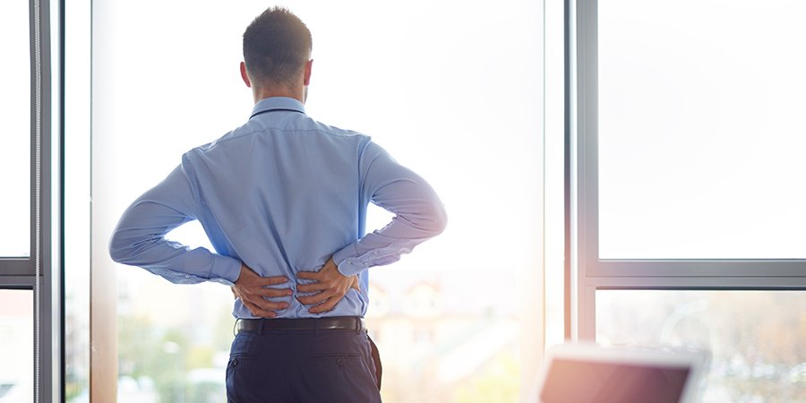 business man with lower back pain. cbd oil for back pain. buy hemp oil for pain online usa.
