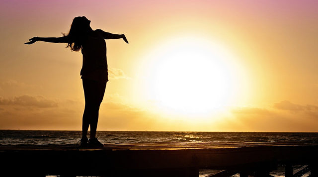 woman relaxing by water at sunset stress free. buy cbd oil online for anxiety.