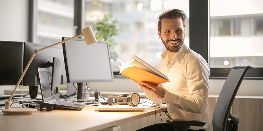 Adult man smiling at desk at work. buy hemp cbd oil for joint pain pain relief.
