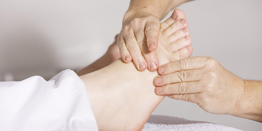 Adult with pain in foot getting a foot massage. cbd oil and nerve pain. cbd cream for nerve pain.
