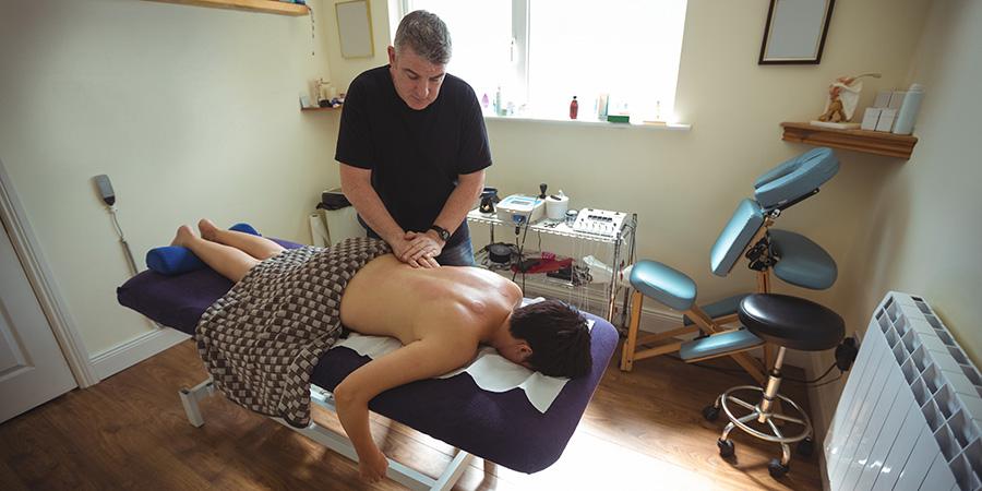 Man receiving a back massage using cbd pain cream. where to buy cbd cream for back pain online.