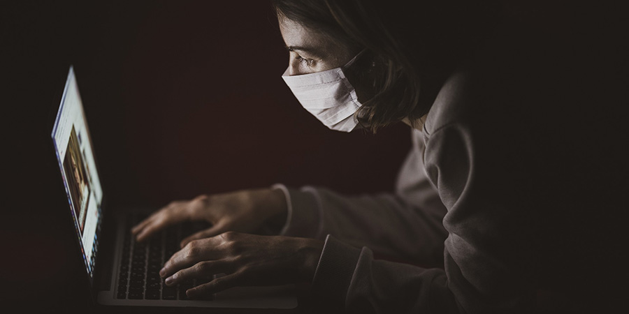 woman with face mask working on laptop in the dark. How many drops of cbd oil for sleep? How much cbd oil to take for sleep? Do hemp products work for insomnia?