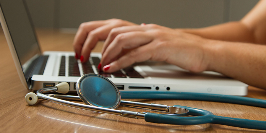 female doctor hands typing on laptop. How to take cbd oil for sleep. when to take cbd oil for sleep.
