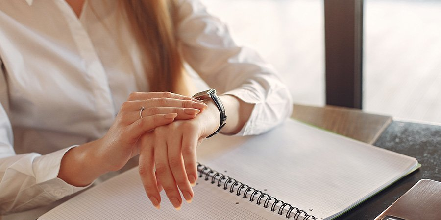 Woman looking at her watch noting when to take her hemp cbd oil extract for sleep.