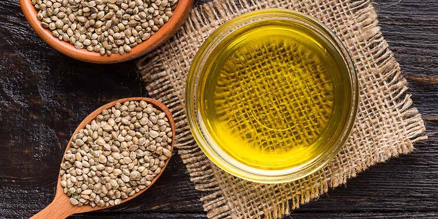 Hemp seeds and oil on wooden background, top view. hemp extract vs cbd CBD Hemp Extract.