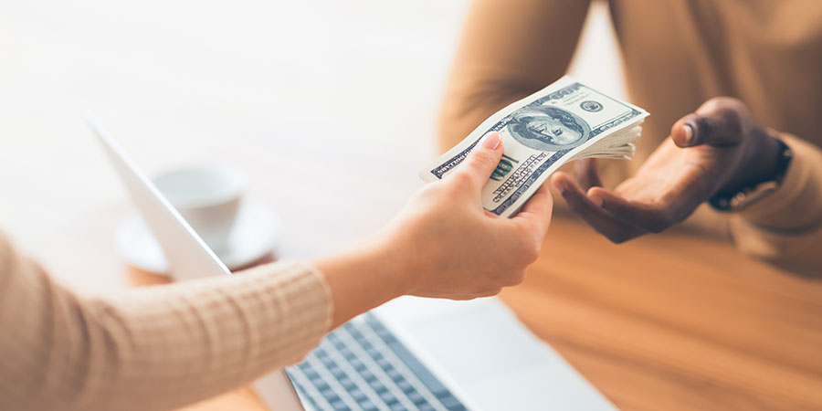 Woman handing cash to a cashier.