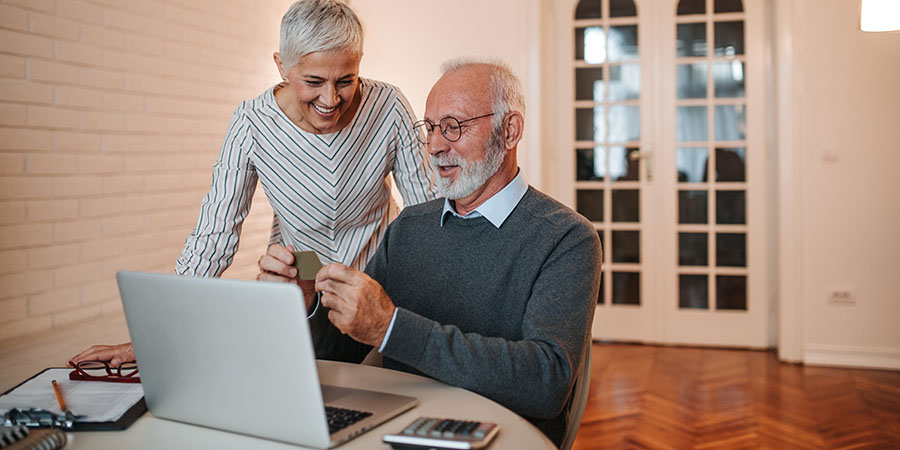 Senior couple shopping online at home.