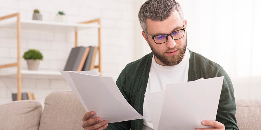 Adult man reading papers.