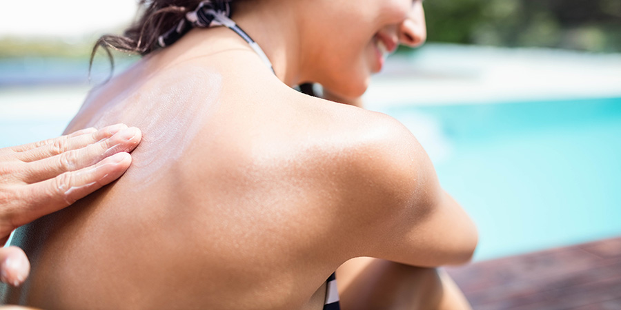 Adult woman getting help cbd cream spread on her back.