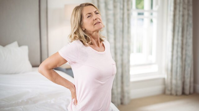 Senior woman having back pain in bedroom at home. How to use cbd oil for back pain. cbd oil and back pain. cbd oil dosage for back pain.