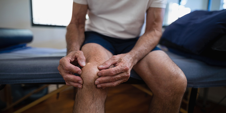 Adult male rubbing his knee in pain. low potency delta 8 thc. Where is delta-8 thc available?