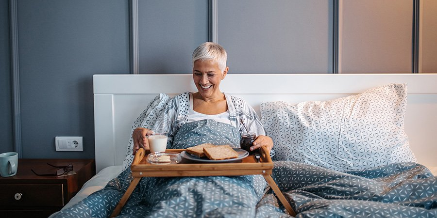Mature woman enjoying breakfast in bed. Does delta 8 thc get you high? Will 8% thc get me high? Will 8 percent thc weed get you high? delta 8 thc high. Buy delta-8 THC online USA.