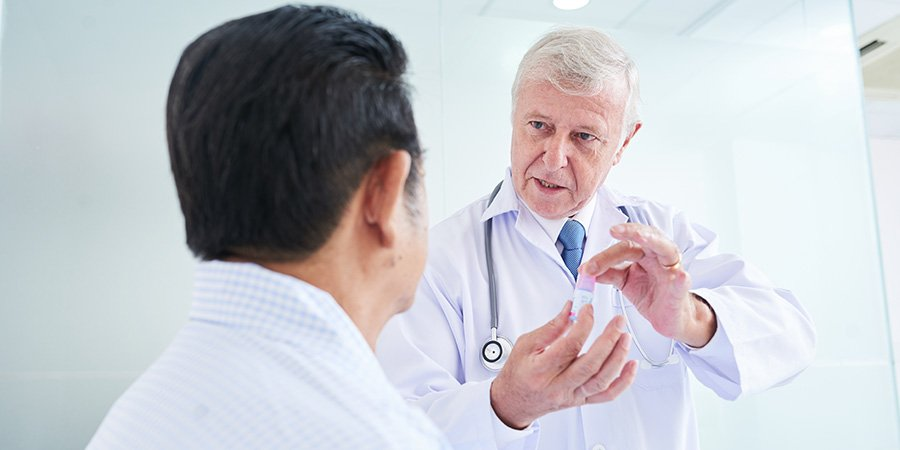 Male doctor discussing how to use topical CBD for nerve pain with patient. Can cbd tincture be used topically for pain? How much topical cbd oil to use for pain?