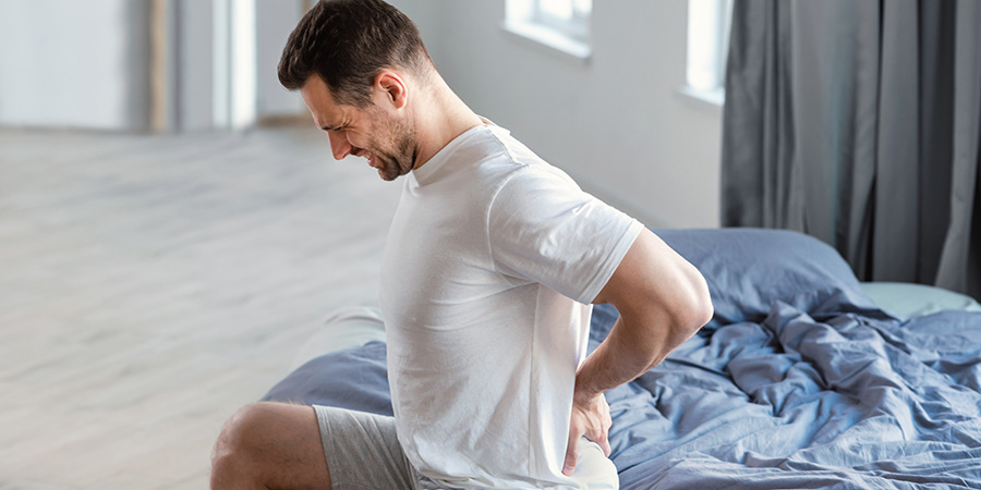 Young fit man showing signs of back pain and nerve pain. How much topical cbd oil to use for pain?