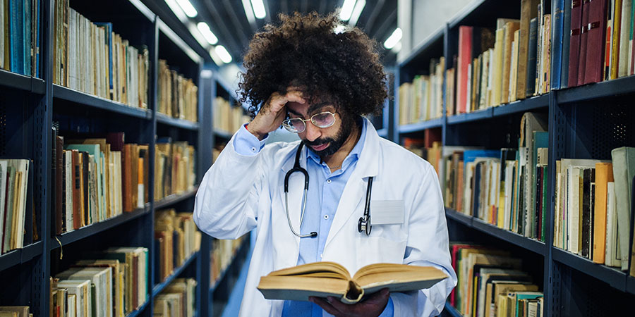 medical student in a library studying how to dose cbd oil.