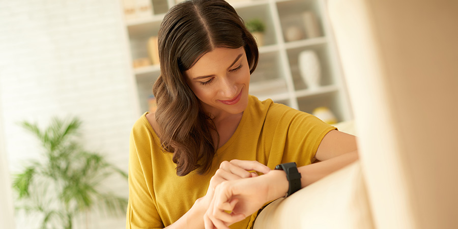 Lovely smiling woman setting her smart watch. Where to buy delta 8 THC snap dragon edibles.