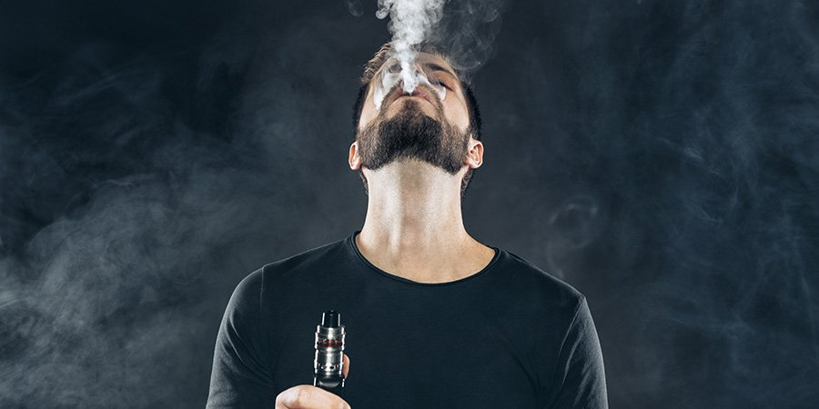 Adult male vaping and blowing smoke clouds. delta vape 2.0 battery for sale.