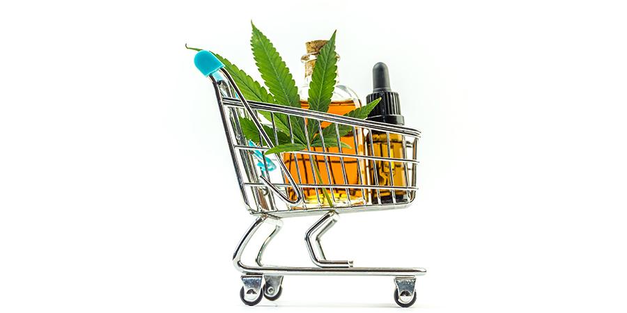 Shopping cart with marijuana leafs and medical cannabis oil cbd.